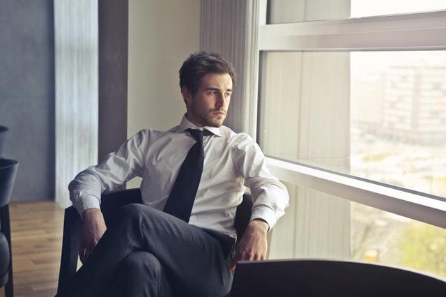 Mladý muž v bielej košeli, tmavých nohaviciach a kravate sedí na stoličke v kancelárii a pozerá von oknom.jpg
