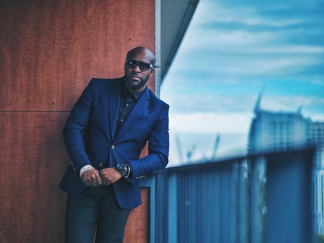 Elegantne oblečený muž v modrom obleku stojí na balkóne.jpg