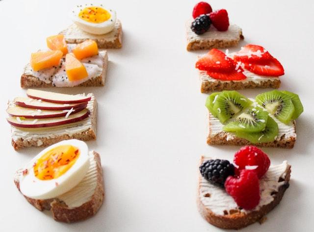 Celozrnné krajce chleba obložené rôznymi druhmi ovocia a vajíčkom