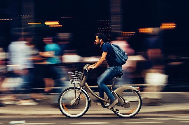 Muž v meste idúci na bicykli