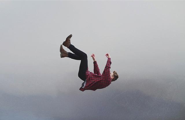 Muž v kockovanej košeli a v čiernych nohaviciach padá voľným pádom z neba