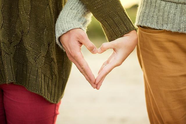 Muž a žena stoja vedľa seba a majú prepletené dlane