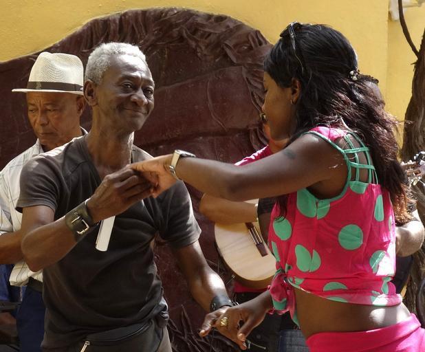Starší muž a žena ho vyzýva k tancu, černosi