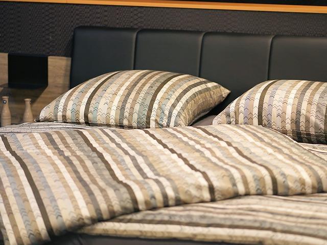 Manželská posteľ s hnedým obliečkami a koženým čelom.jpg