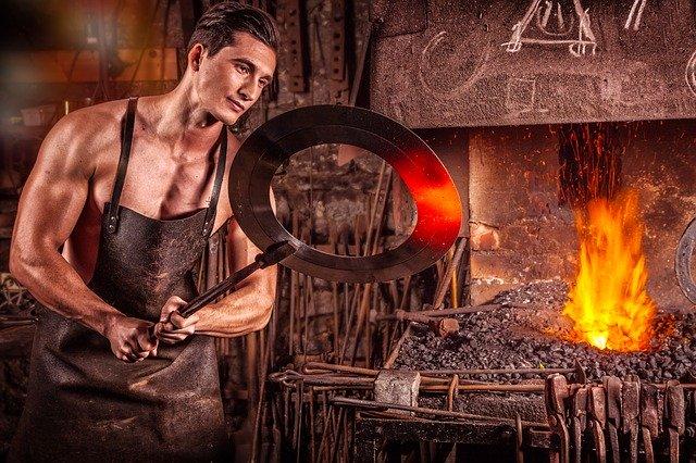 Muž vyberá z pece kus železa, ktorý kove.jpg