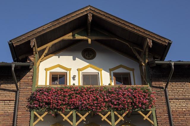 Balkónové zábradlie na balkóne rodinného domu obrastené červenými kvetmi.jpg