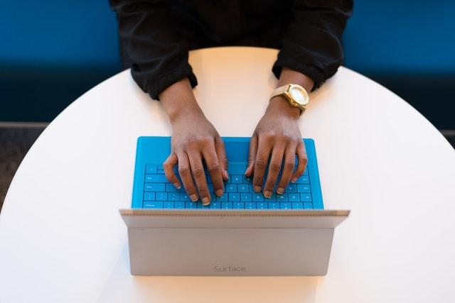Človek s hnedou pokožkou píše na notebooku s tyrkysovou klávesnicou